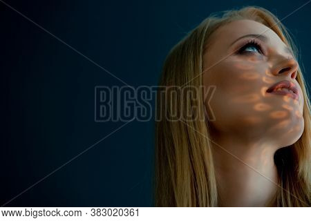 Beautiful mid adult woman with interesting pattern of light and shadow on her face. Beauty female portrait.