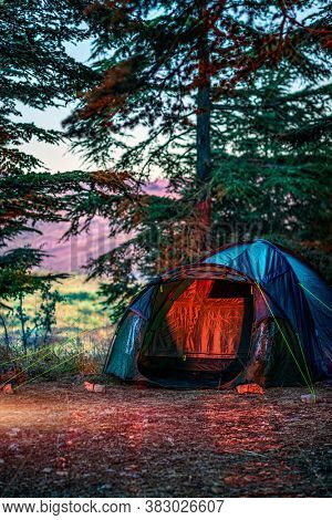 Camping Tent Standing in the Beautiful Cedars Forest in the Mountains. People Sleeping in the Forest. Enjoying Nature and Active Life.