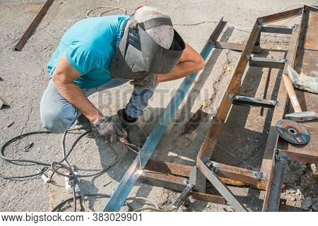 Welder Welds Metal Structure. Construction Worker At Work. A Working Welder Builds Or Repairs A New