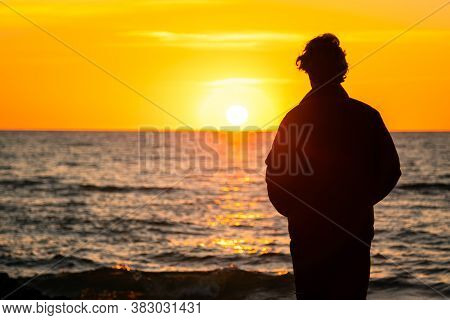 Dark Silhouette Of A Man Standing By The Sea At Golden Sunset. Lonely Teenager Looking A Setting Sun