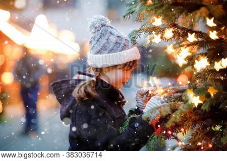 Little Cute Kid Girl Having Fun On Traditional Christmas Market During Strong Snowfall. Happy Child