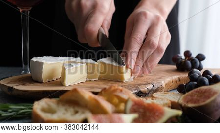 Slicing Camembert Cheese. Wine Appetizer Plate Or Cheese Plate With Figs, Grapes, Baguette And Soft