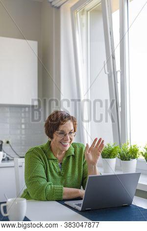Senior Woman Having Online Conversation In Home Interior.