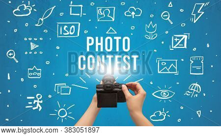 Hand taking picture with digital camera and PHOTO CONTEST inscription, camera settings concept
