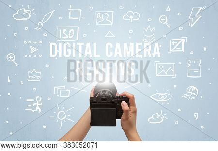 Hand taking picture with digital camera and DIGITAL CAMERA REVIEWS inscription, camera settings concept