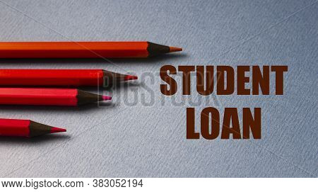 Student Loan - Text On Gray Paper With Red Pencils Lying Next To. Finance And Education Concept