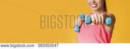 Closeup Of Unrecognizable Girl Doing Workout Training With Dumbbells, Standing Over Yellow Backgroun