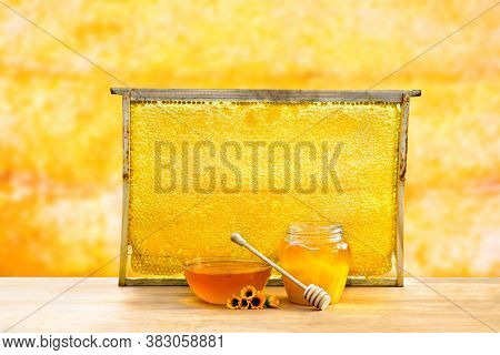 Honey In Glass Bowl, Wooden Honey Dipper And Honeycombs In Wooden Frame With Full Cells Of Honey Sea