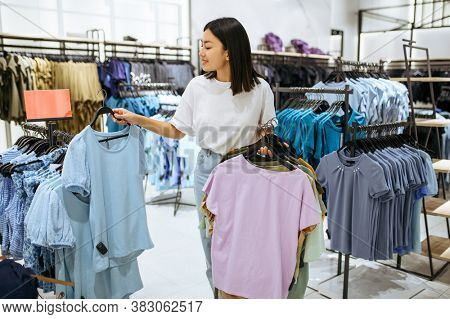 Woman holds clothes on hanger in clothing store