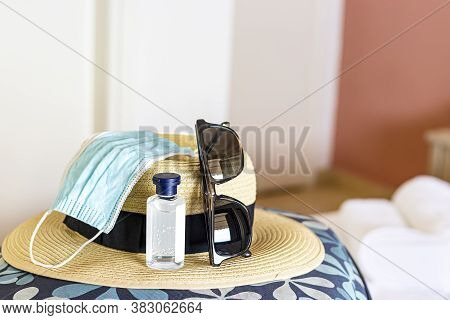 A Straw Hat On A Bag With A Mask, Hand Sanitiser And Sunglasses.