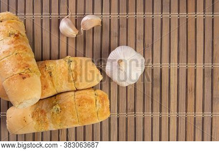 Garlic Bread Stuffed With Cheese Arranged On A Bamboo Mat With Garlic Around It On A Table, Top View