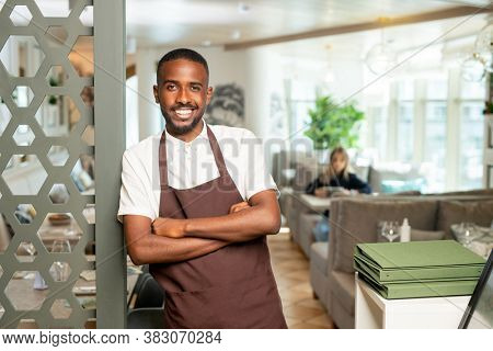 Cheerful young African waiter in workwear leaning against door inside contemporary restaurant while waiting for new guests