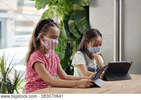 Asian And Caucasian Little Girls With Tablet Devices Indoors