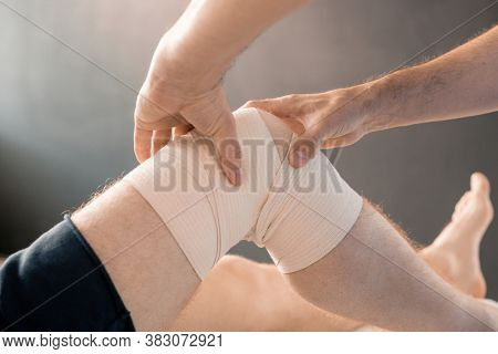 Hands of contemporary clinician massaging knee of young male patient wrapped with flexible bandage during rehabilitation course