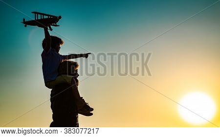 Success And Child Leader Concept. Sunset Silhouette Of Father And Son Together. Boy Child Is Sitting