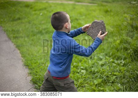 The Child Throws A Stone. The Boy Took The Cobblestone In His Hands. Renok Is Showing Aggression. A