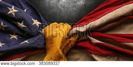 Worn work glove holding old US American flag. Made in USA, American workforce, blue collar worker, or Labor Day concept.