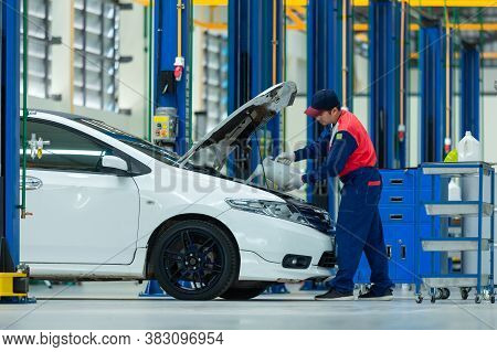 Asian Servicing Mechanic Pouring New Oil Lubricant Into The Car Engine In The Auto Repair Center