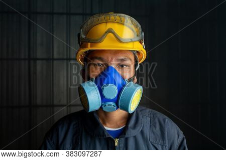 Asian Worker Wear Wears A Respirator In A Smokey, Toxic Atmosphere. Image Show The Importance Of Pro