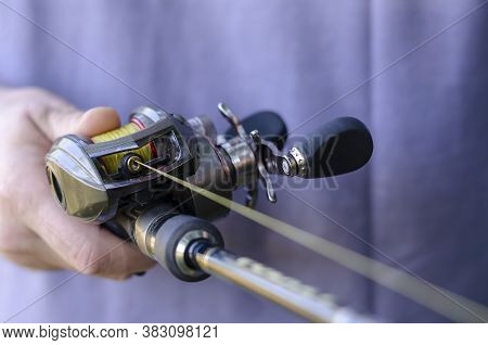 Close-up Of Male Hand With A Fishing Rod And Baitcasting Reel. Caucasian Man Is Fishing With Casting