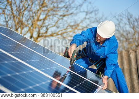 Man Worker In Blue Suit And Protective Helmet Installing Solar Photovoltaic Panel System Using Screw