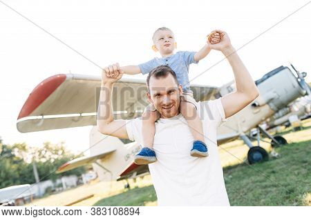A Dad And Toddler Spend Time Outdoors In An Airplanes Museum. A Young Father Carries Baby Boy On His