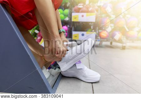 Little Girl Tried Shoe In Front Of Mirror In Shopping Mall. Asian Girl Smileing Happy To Choice And