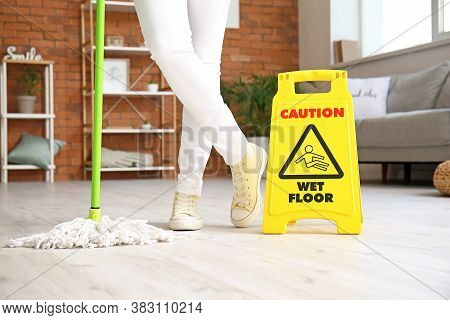 Young Woman Mopping Floor In A Room