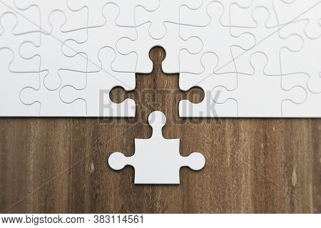 Incomplete Puzzles On Wooden Table. Business And Teamwork Concept. 3d Rendering