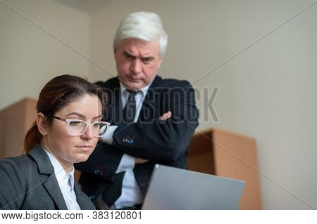 The Male Boss Supervises The Work Of The Female Subordinate At The Laptop.