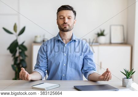 Office Zen. Relaxed Male Entrepreneur Meditating At Workplace, Coping With Stress At Work, Sitting A