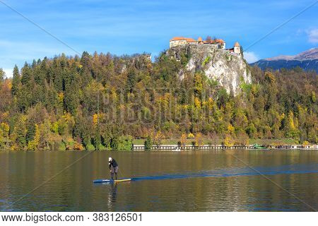 Bled, Slovenia - October 31, 2018: Man On Paddle Board On Lake Bled And Autumn Colorful Trees Backgr