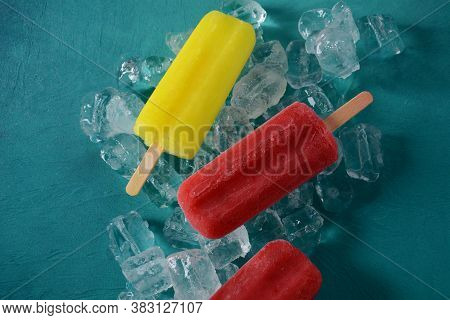 Strawberry Popsicle And Lemon Popsicle On Blue Background With Ice