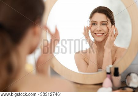 Eye Care Routine. Young Woman Massaging Eye Zone, Looking At Mirror, Home Interior