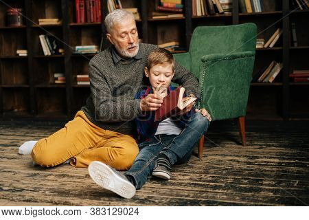 Mature Grandfather And Little Grandson Reading Interesting Book Together Sitting On Floor On Home Li