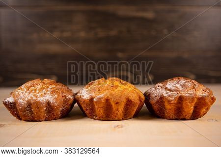 Freshly Baked Muffins Muffins In Powdered Sugar On A Wooden Background. Home Baking As A Cooking Or