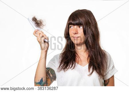 A Woman With Tattoos, Holding A Comb With A Tuft Of Torn Hair. White Background. The Concept Of Loss