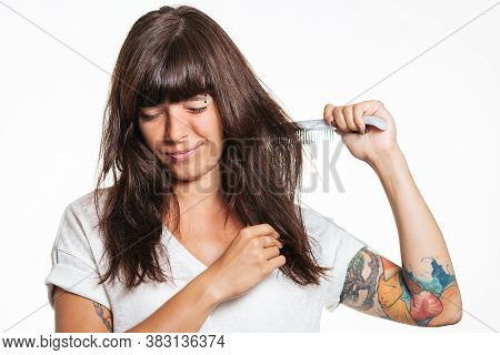 Portrait Of A Tattooed Woman Combs Her Hair In Pain And Rips It Out. White Background. The Concept O