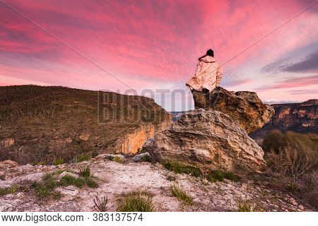 Woman With The Best Views, Sitting On A Rock Overlooking The Escarpment Cliffs And Valleys Watching