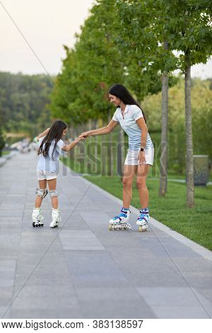 Young Mother And Her Cute Little Daughter Rollerskating In Summer Park. Happy Family Have Fun
