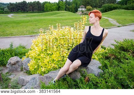 Young, Short-haired, Redhaired Woman In A Black Dress Sits On A Stone In A Park, Against The Backgro