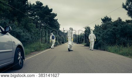 People With Bacteriological Protection Suits Walking On A Road Looking For Evidence