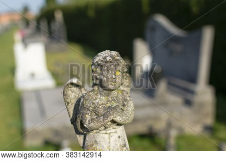 Weathered Concrete Statue Of An Angel In A Children's Cemetery