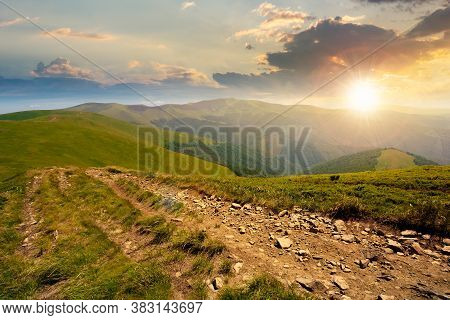 Mountain Road Through Grassy Meadow At Sunset. Wonderful Autumn Adventure In Evening Light. Clouds O