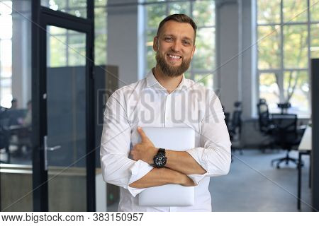 Young Handsome Businessman Smiling In An Office Environment.