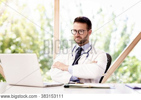 Thinking Male Doctor Sitting In The Doctor's Office