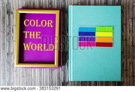 Text Color The World On A Colorful Notebook In A Frame, Next To A Colored Notebook And Colorful Stic