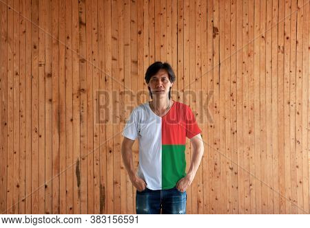 Man Wearing Madagascar Flag Color Shirt And Standing With Two Hands In Pant Pockets On The Wooden Wa
