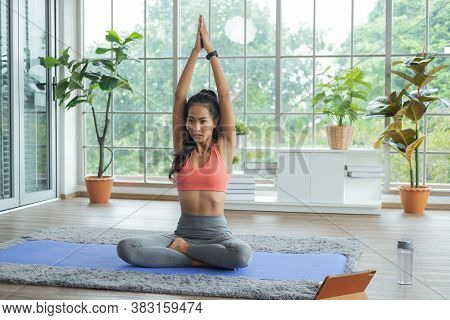 Training At Home. Young Asian Woman Doing Yoga Exercises With Meditating, Breathing And Relaxing, Wh