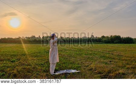 A Muslim Senior Man Wearing An Embroidered Skullcap And White Traditional Clothes Prays At Sunset In